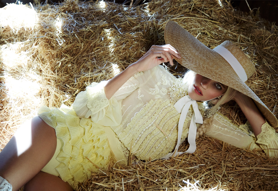 Woman lying on straw in Elisabetta Franchi Dress and Hat